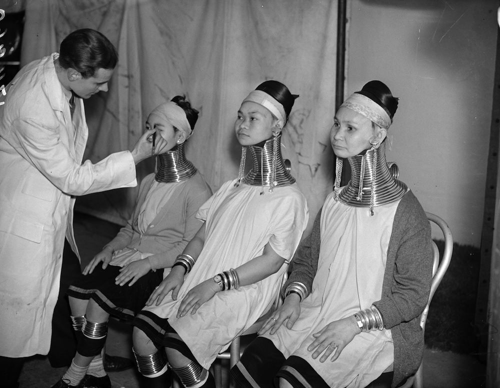 4th November 1937:  Three women from the Shan States between Tibet and Upper Burma who elongate their necks with metal bands are being made up in for a film test. They came to England to work with Bertram Mills circus.  (Photo by Harry Todd/Fox Photos/Getty Images)