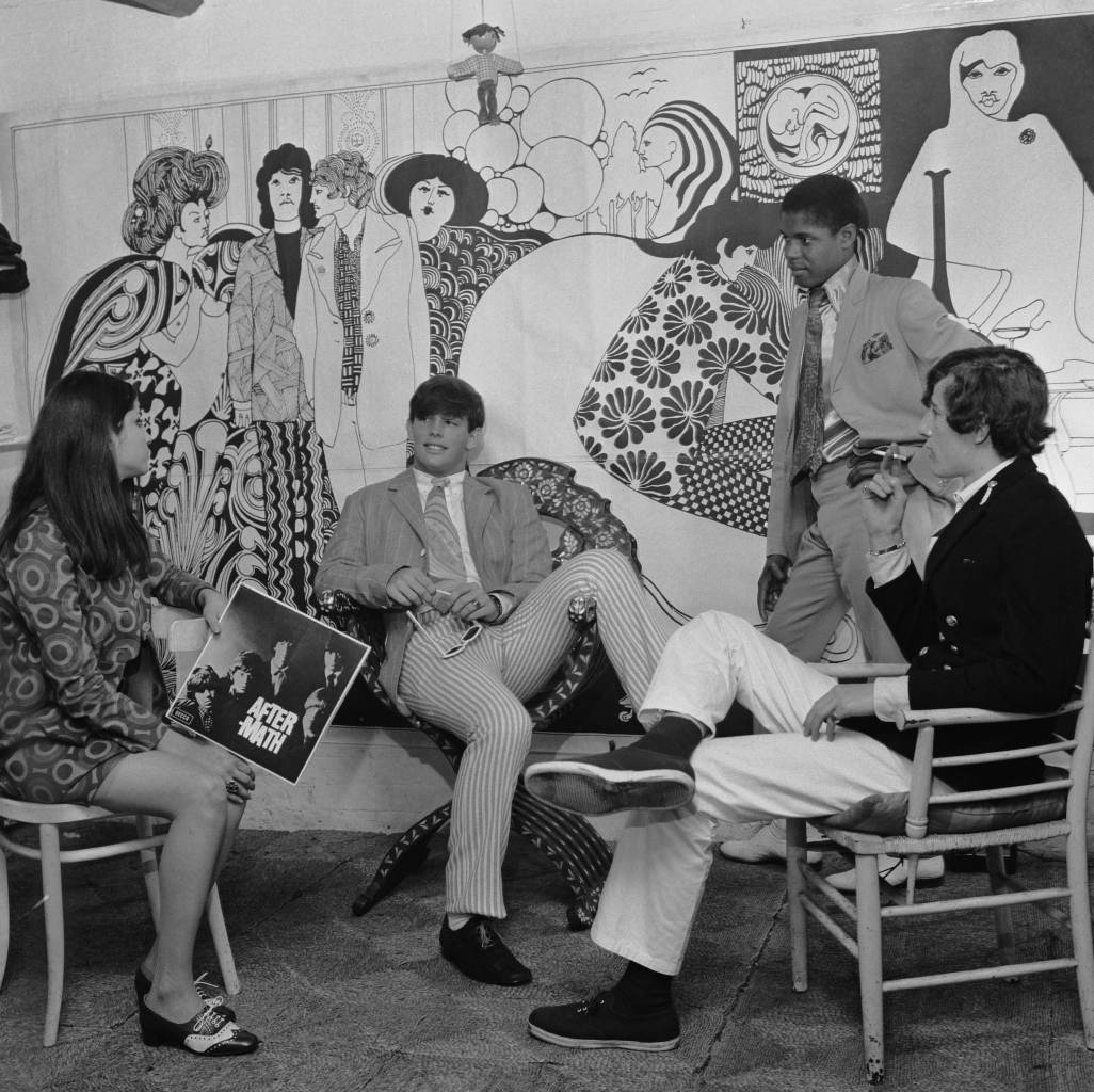19th July 1966:  Fab fellers and groovy chicks hang out together at 'Hung On You' boutique in Chelsea's Cale Street, London. No shopping experience would be complete without a copy of the Rolling Stones' album 'Aftermath' in your hand. The mural is by Albert Little. (Photo by Evening Standard/Getty Images)