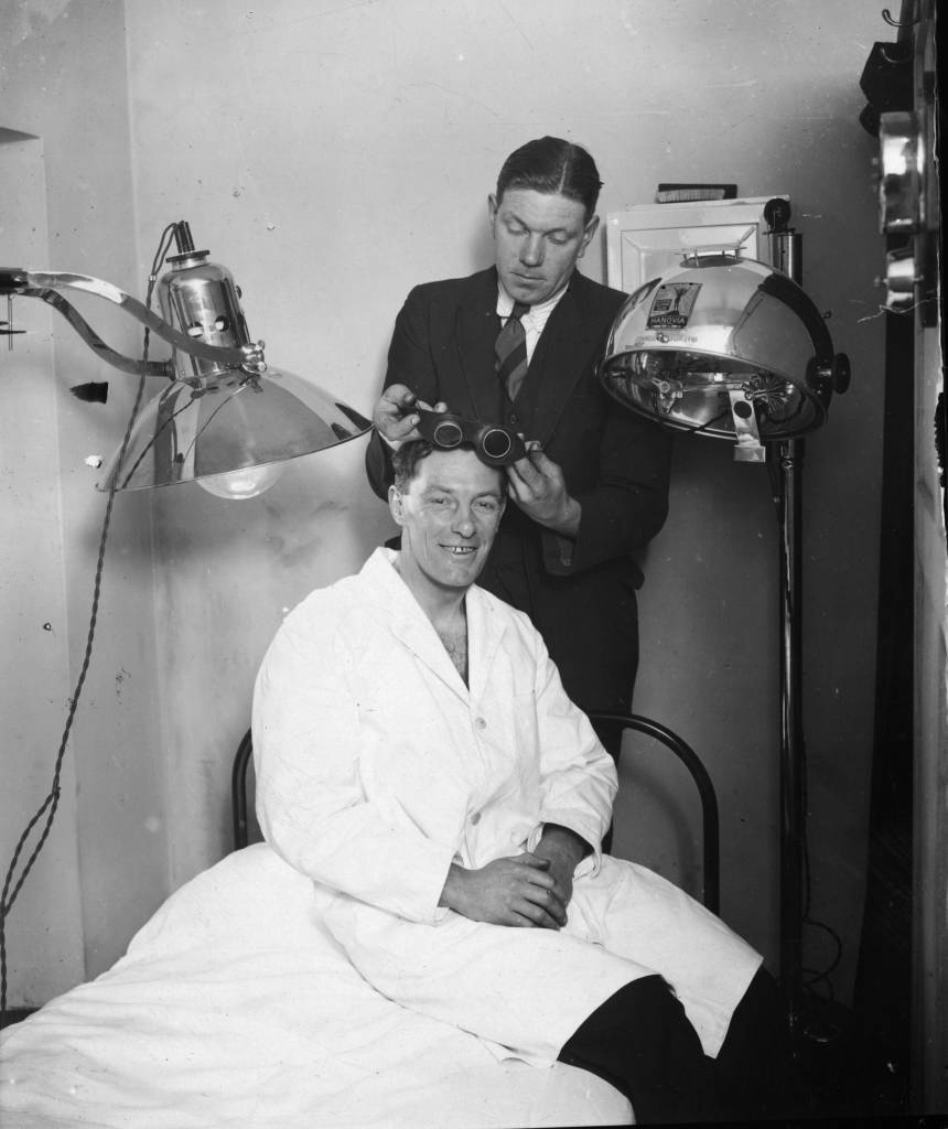 7th February 1929:  Northampton Town Football Club trainer fits the team captain, W Watson, with some goggles for a course of ultra-violet ray treatment in preparation for an FA Cup tie with Millwall.  (Photo by Crouch/Topical Press Agency/Getty Images)