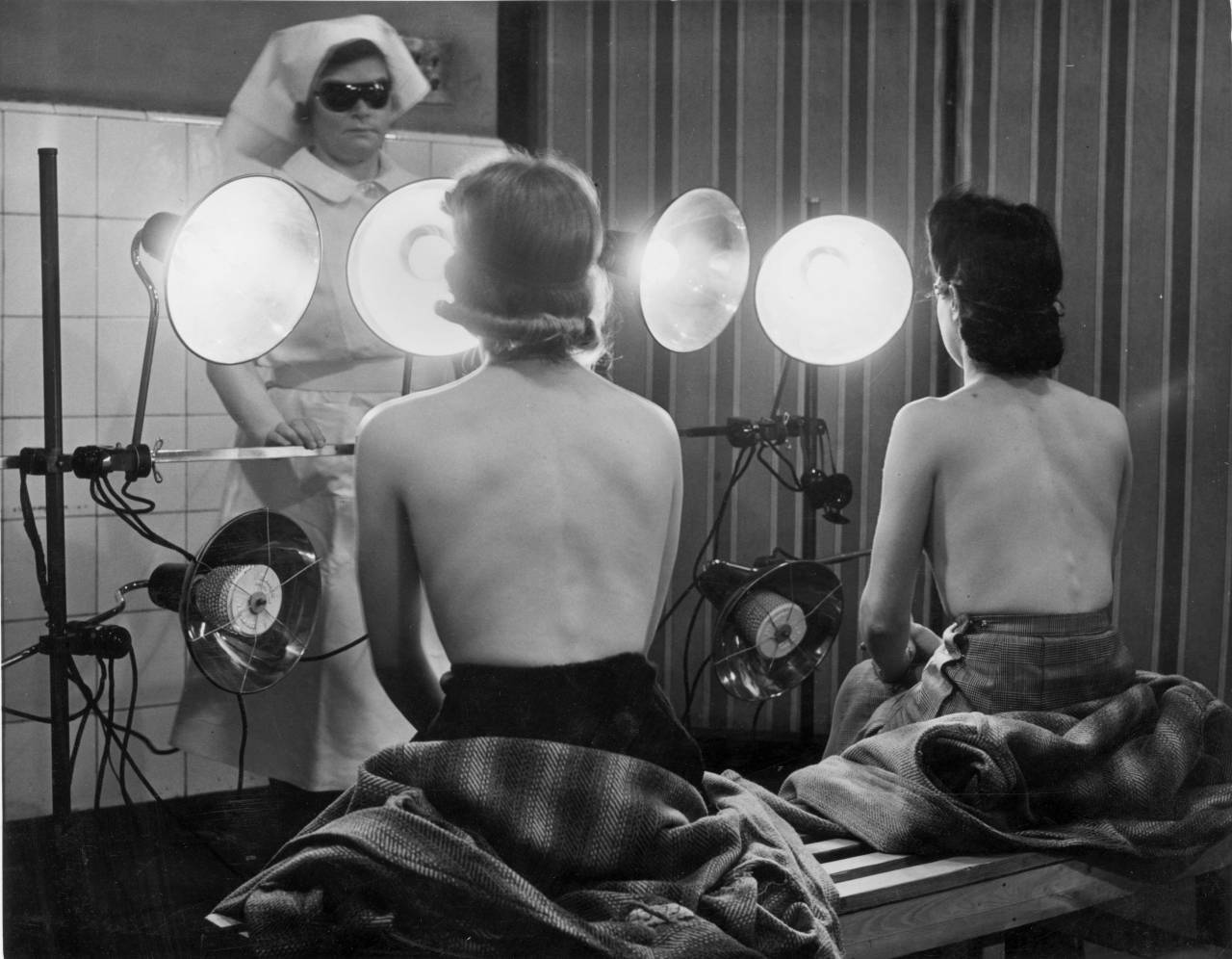17th April 1942:  Civil Defence Workers in Finsbury are beating the winter pallor with free sun lamp treatments. They call it 'Mixray' at the Finsbury Health Centre, and it was designed by two Czechoslovak inventors.  (Photo by Harry Todd/Fox Photos/Getty Images)