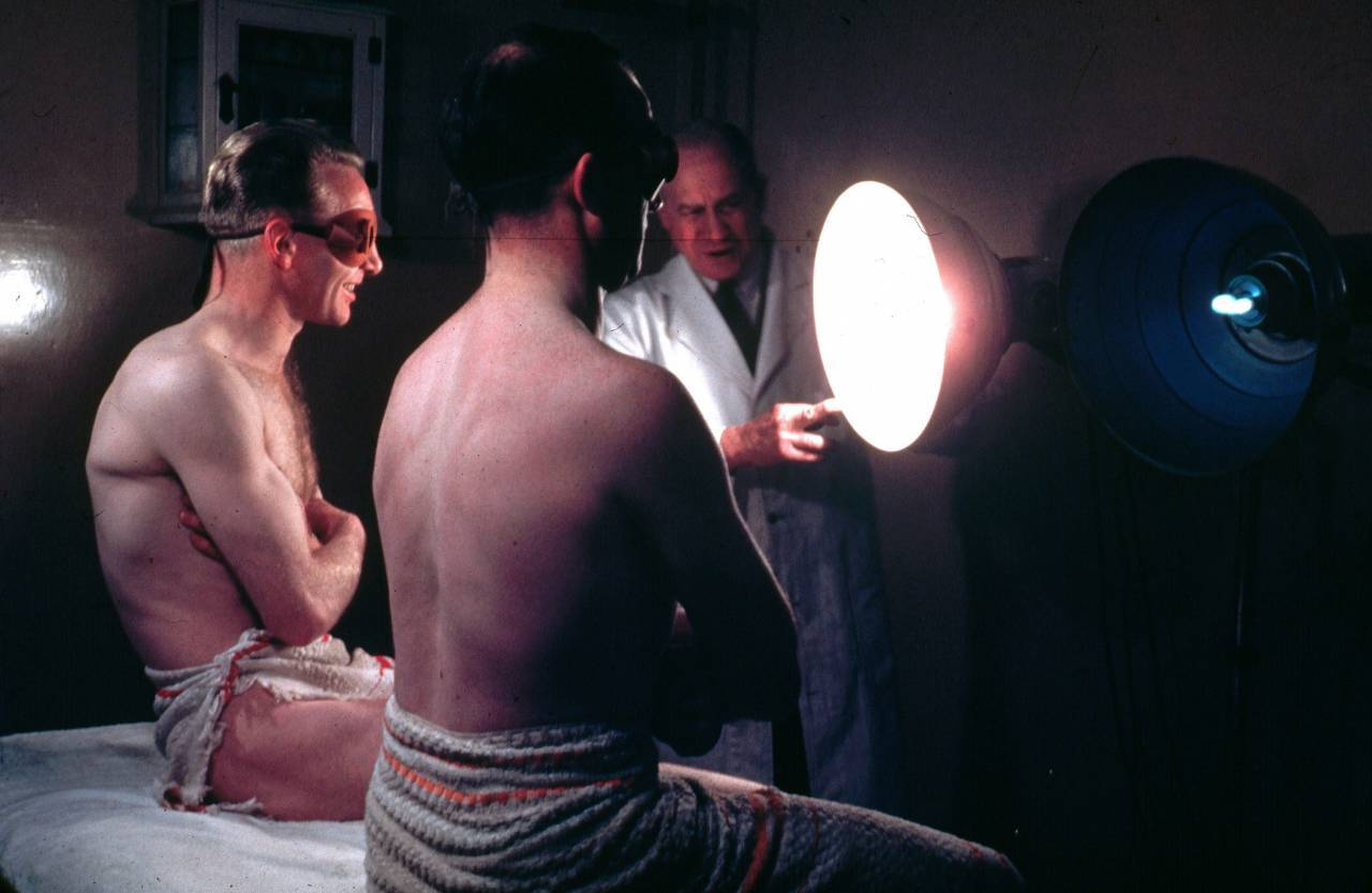 circa 1950:  Two men wearing protective eye goggles and towels sitting under sunlamps set up by a doctor.  (Photo by Hulton Archive/Getty Images)
