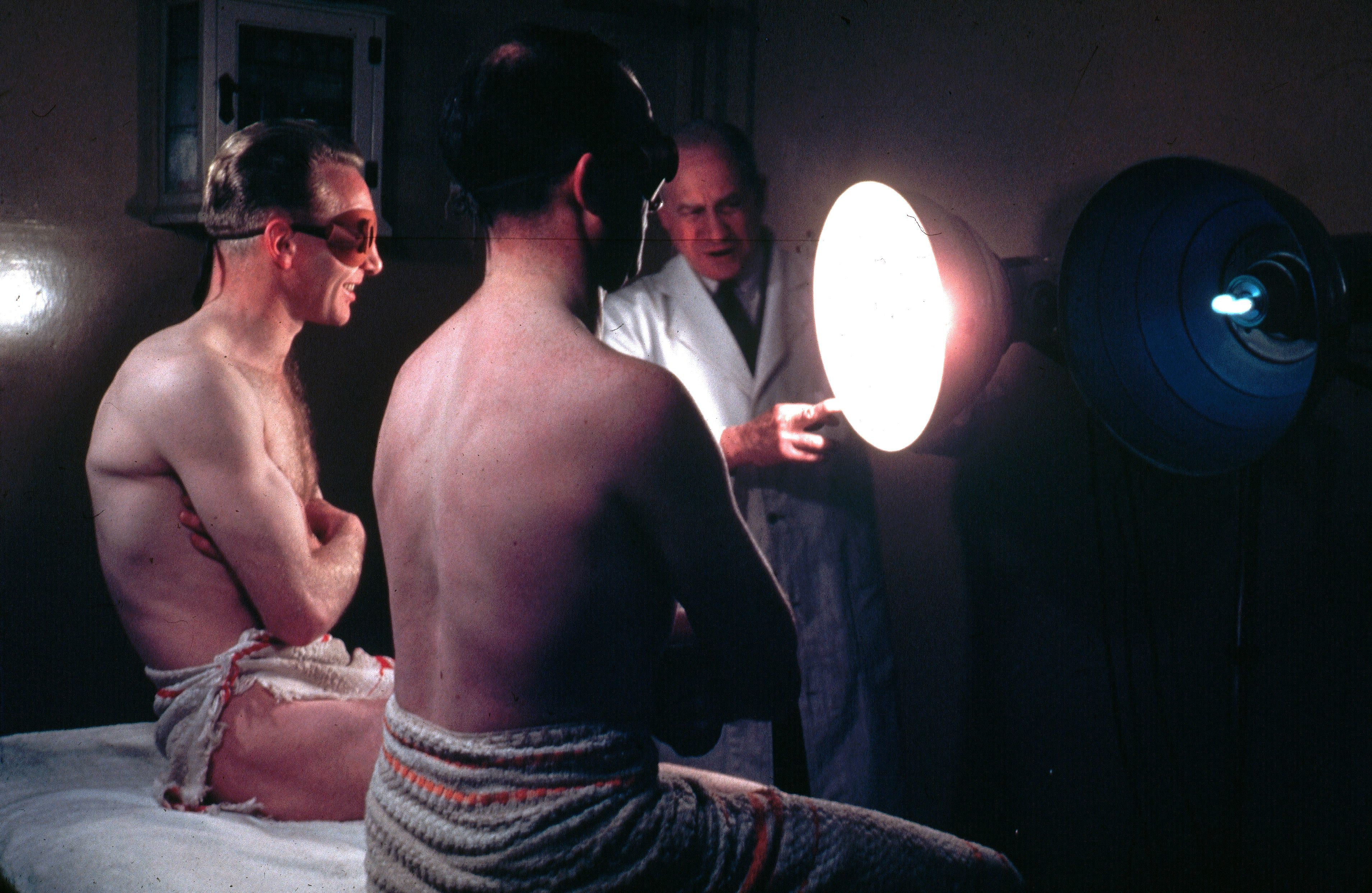 Circa 1950: Two Men Wearing Protective Eye Goggles And Towels Sitting Under  Sunlamps Set Up
