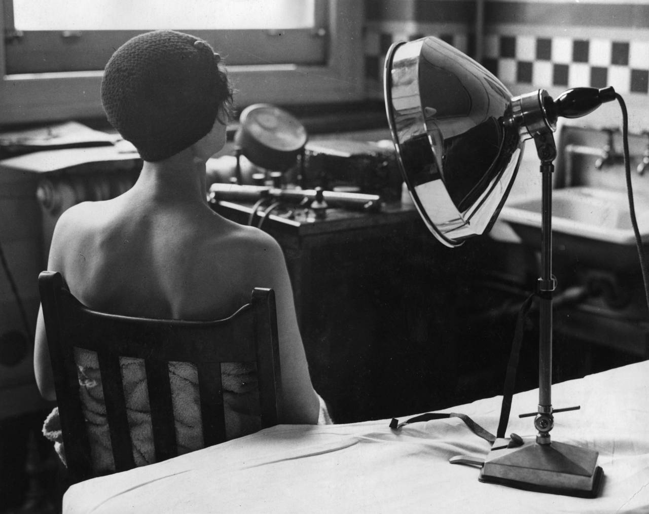 circa 1932:  Using an infra-red ray lamp to cure skin complaints.  (Photo by Fox Photos/Getty Images)
