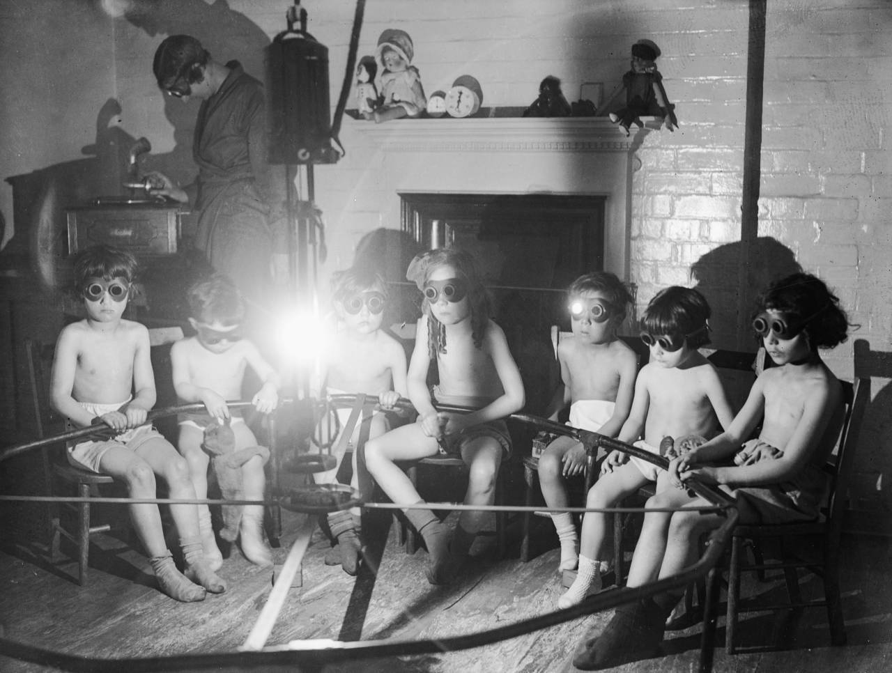 11th May 1931:  Stripped to the waist and wearing goggles, children sit round a lamp having sun ray treatment while they listen to the gramophone at the East End Mission in Commercial Rd, London.  (Photo by Fox Photos/Getty Images)
