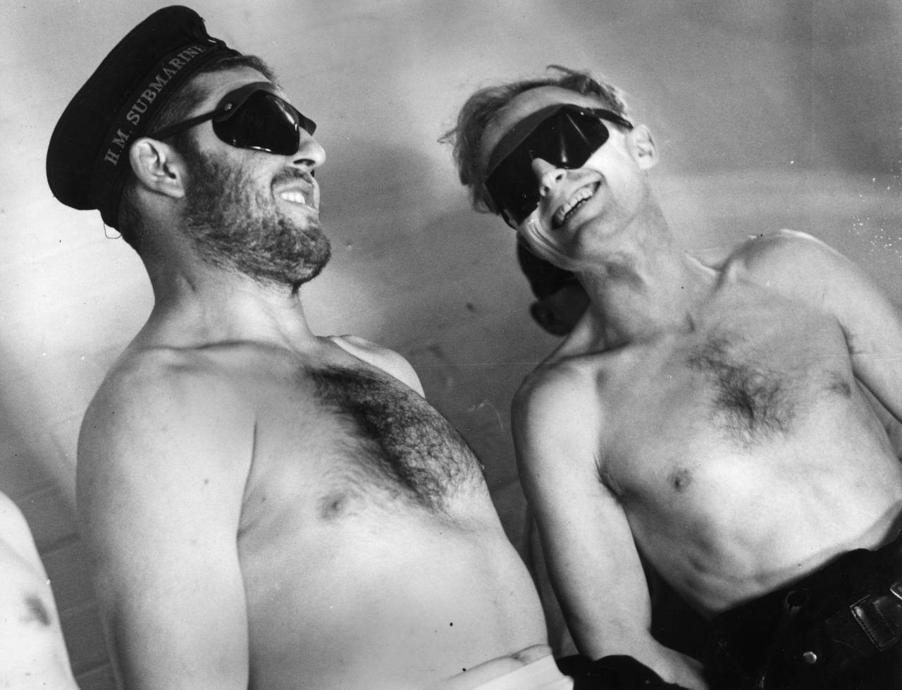 13th December 1940:  Two crew members of a British submarine spend a session under a sunlamp whilst ashore, to make up for the time they spend below the surface without being subjected to sunlight.  (Photo by Arthur Tanner/Fox Photos/Getty Images)