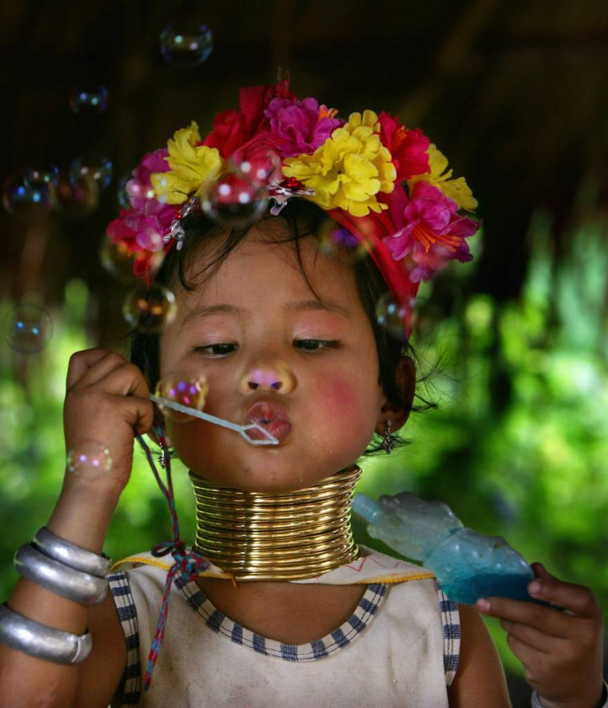 CHIANG DAO, THAILAND - JULY 13:  Paeng , 5, who is a Long Neck  Padaung hill tribe girl,  blows bubbles in a small village where 30 familes live July 13, 2006 in Chiang Dao, Thailand. All the Long Neck villages are set up for tourists and just over a year ago the hill tribe members were hand picked to move closer to Chiang Mai from more remote communities so that they could be more accessible. The Padaung women famously wear brass rings around their necks, beginning at five-years-old, to distort the growth of their collarbones and making them look like they have long necks. They are originally from eastern Burma near the Thailand border.  (Photo by Paula Bronstein/Getty Images)
