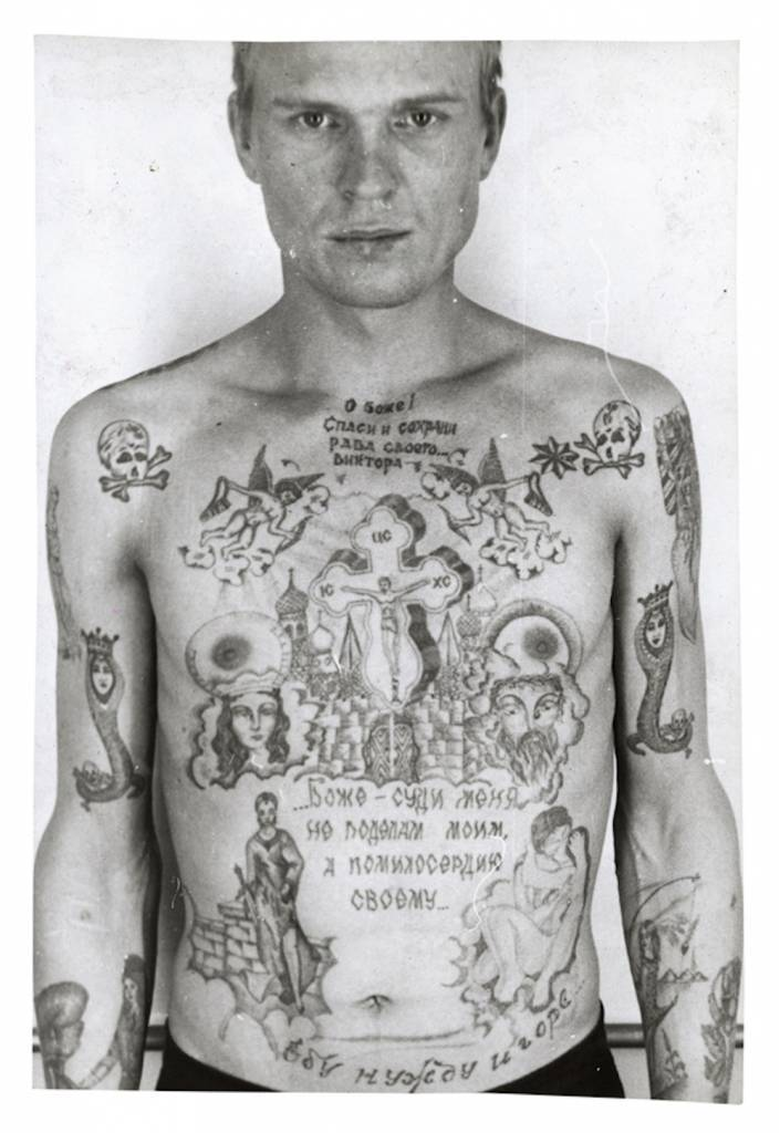 Text above the cross reads 'O Lord, Save and Protect your servant Viktor', text beneath reads 'God do not judge me by my deeds but by your mercy'. Text above the waist reads 'I fuck poverty and misfortune'. The skull and crossbones show that the prisoner is serving a life term. The single eight-pointed star denotes that he is a 'semi-authority' among thieves. The girl 'catching' her dress with a fishing line on his left forearm is a tattoo worn by hooligans and rapists. The snake coiled around human remains (positioned on the middle third of each arm) is a variation on an old thieves' tattoo. The snake is a symbol of temptation; here the snake's head has been replaced by that of a woman: the temptress. Tattooed on the right side of the stomach is a version of Judith (1504) as painted by Giorgione: this is intended as a symbol of a scheming, seductive woman who betrays a noble man.    © Arkady Bronnikov / FUEL