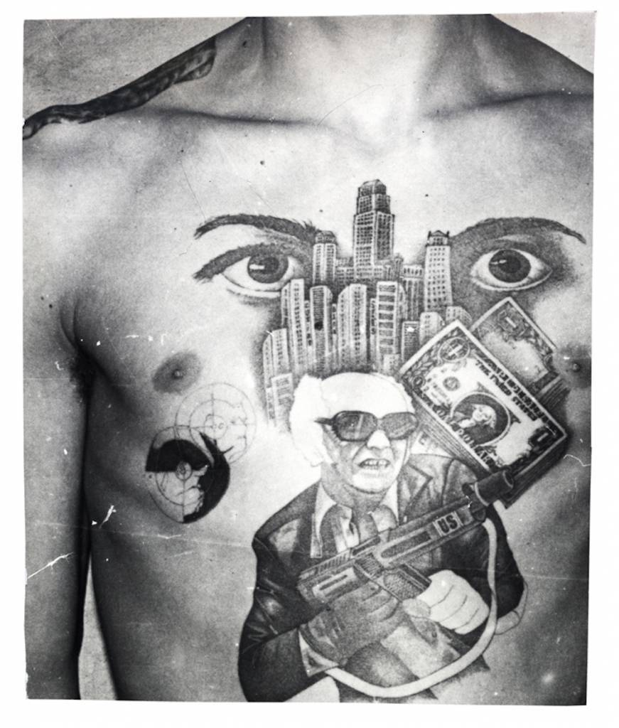The man in this tattoo is a character from a TV crime series shown during the Soviet era – a brutal gang leader. In the story, he ends up in jail. In this tattoo, however, he defends himself against the Soviet power and fights back. On his submachine gun are the letters 'US' which along with the skyscrapers and dollar bills embody the ideological opponents of the Soviet Union and indicate a hatred of the government. The eyes signify that 'I am watching over you' (the other inmates in the prison or camp). The epaulette tattooed on the shoulder denotes the inmates 'rank' among the criminal caste. © Arkady Bronnikov / FUEL