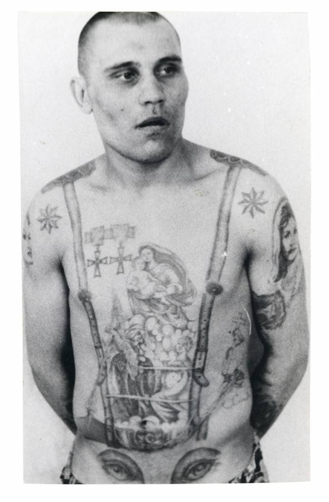 The stars on the shoulders show that this inmate is a criminal 'authority'. The medals are awards that existed before the Revolution and as such are a sign of antagonism and defiance towards the Soviet regime. The eyes on the stomach denote a homosexual (the penis makes the 'nose' of the face). © Arkady Bronnikov / FUEL