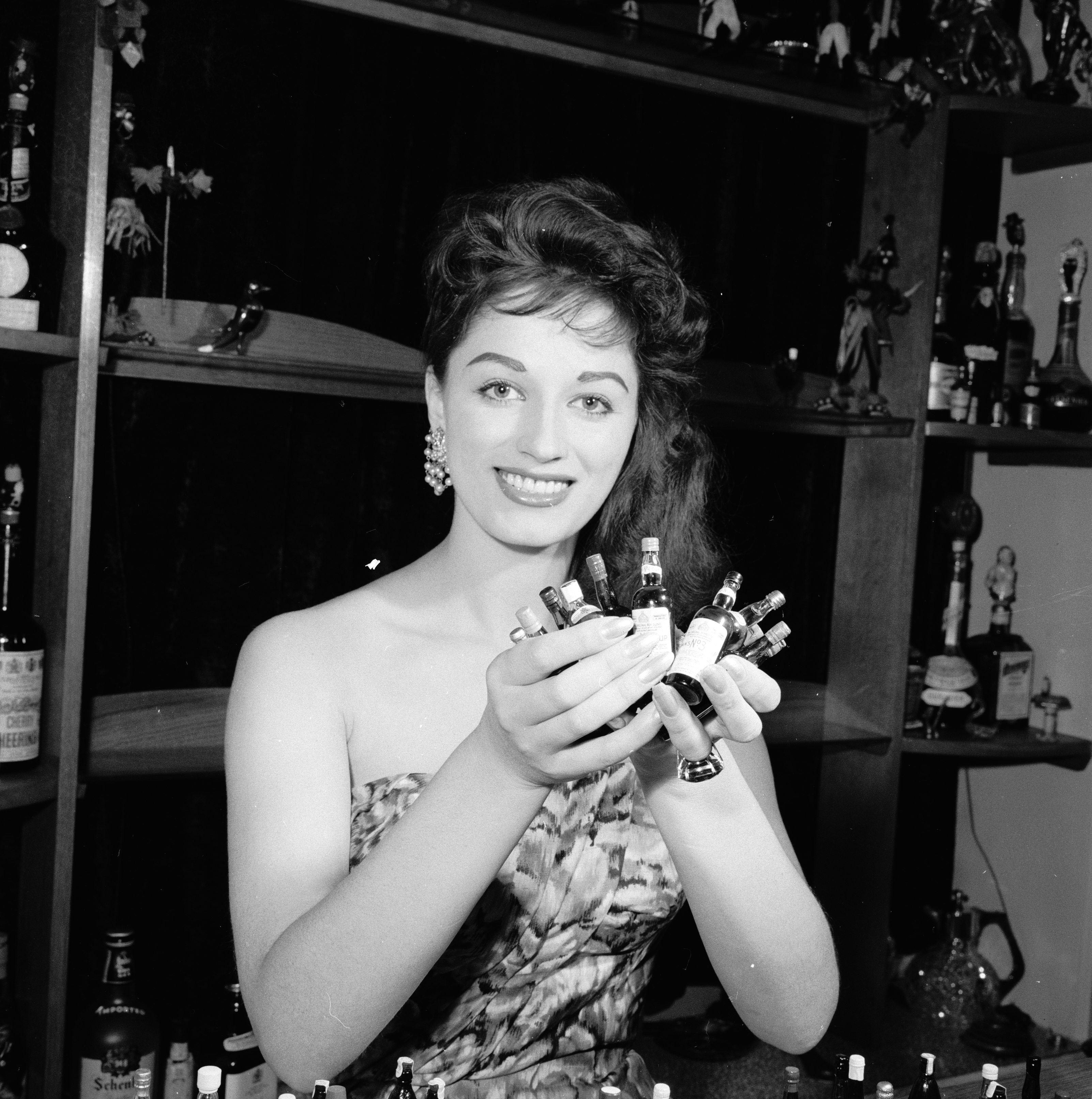 September 1958:  English actress and novelist Jackie Collins at the cocktail bar in her home in London proudly displaying her collection of miniature bottles.  (Photo by Frank Martin/BIPs/Getty Images)