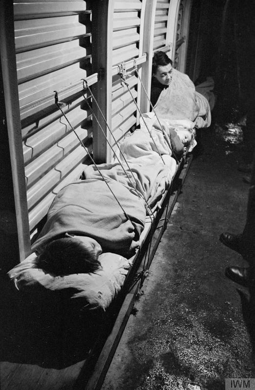 Two children sleep on a bench in a trench shelter by Bill Brandt