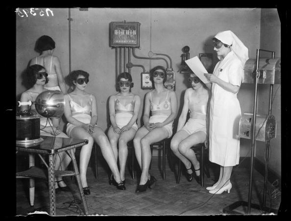 UNITED KINGDOM - NOVEMBER 21: Sunray 'treatment', 1932. A photograph of women receiving sunray 'treatment', taken by Cardew for the Daily Herald newspaper on 20 February, 1932. These women, all Metropole Cinema attendants, enjoy a tanning session in a 1930s solarium. As they sit in front of the sunlamps, goggles protect their eyes - and a nurse is on hand to ensure no one is overexposed to the ultraviolet light. This photograph has been selected from the Daily Herald Archive, a collection of over three million photographs. The archive holds work of international, national and local importance by both staff and agency photographers. (Photo by Daily Herald Archive/SSPL/Getty Images)