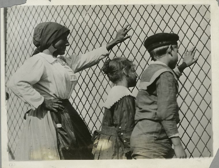 A woman, a boy and a girl at a chain link fence, Ellis Island, New York
