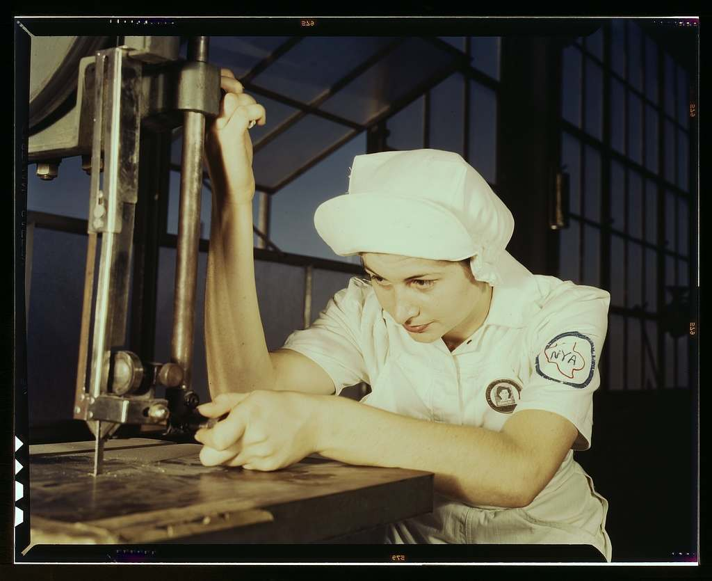 """""""Women in white"""" doctor Navy planes (motors) at the Naval Air Base, Corpus Christi, Texas. Mildred Webb, an NYA trainee at the base, is learning to operate a cutting machine in the Assembly and Repair Department. After about eight weeks as an apprentice she will be eligible for a civil service job in the capacity for which she has been trained"""