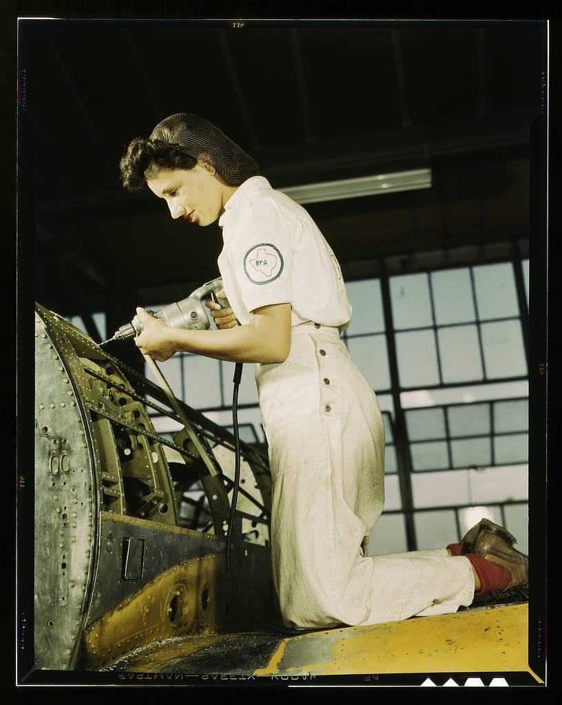Oyida Peaks riveting as part of her NYA training to become a mechanic at the Naval Air Base, in the Assembly and Repair Department, Corpus Christi, Texas