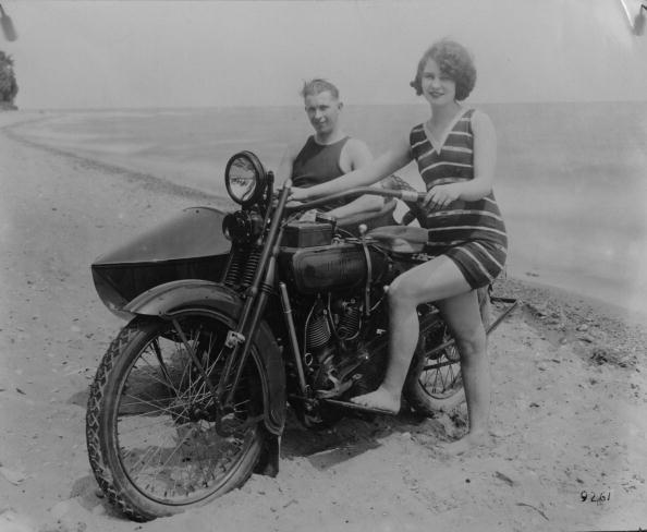circa 1925:  A woman on a beach in California with her Harley Davidson and boyfriend, who is sitting in the side car.  (Photo by General Photographic Agency/Getty Images)