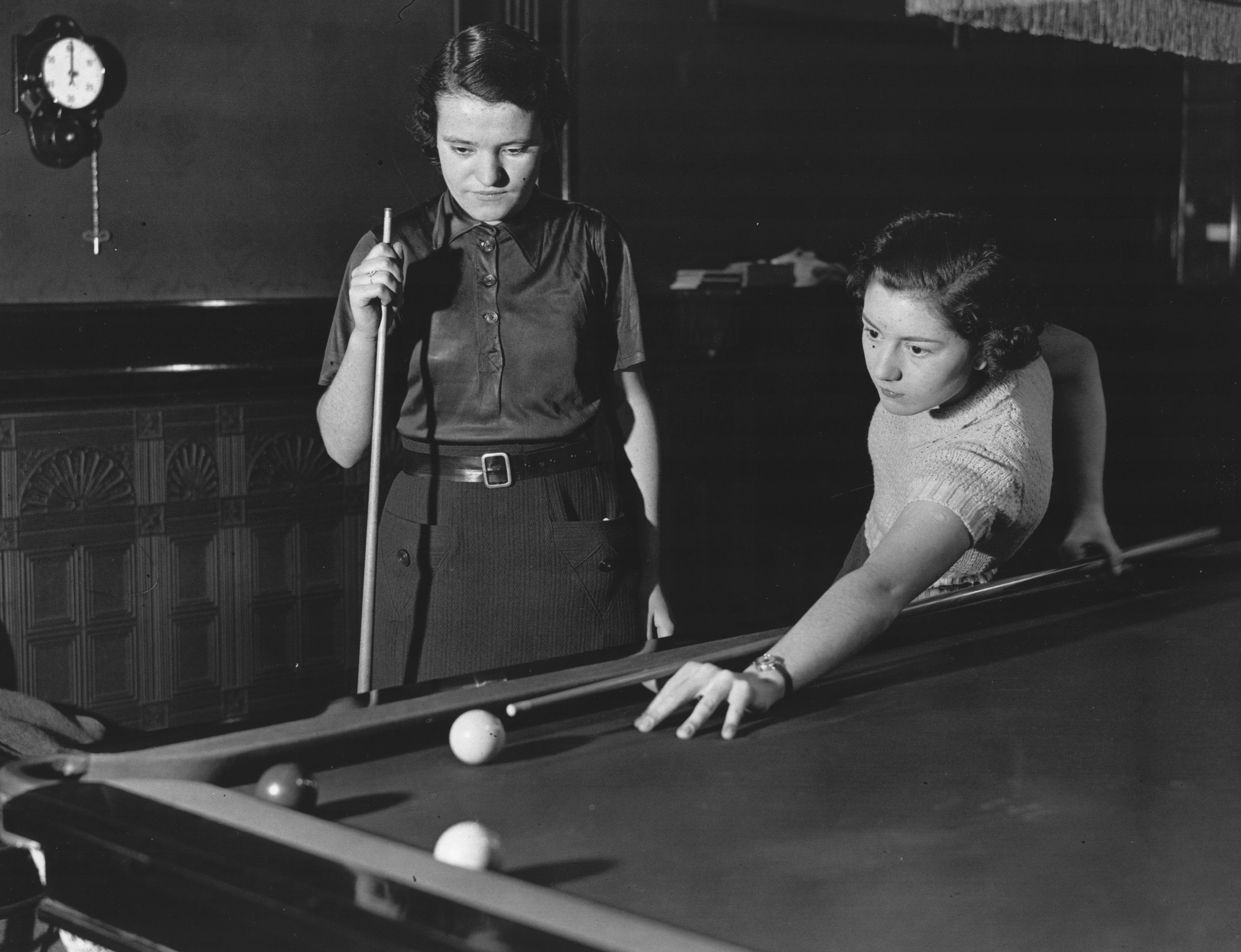 4th January 1934:  Helen McDougall prepares to play a tricky shot  at the women's billiard hall in Soho, while her mother watches.  (Photo by Keystone/Hulton Archive/Getty Images)
