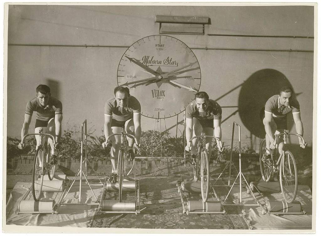 Four cyclists on speed bicycles on rollers time trials to promote Malvern Star: from left, Lennie Rogers, Bill Moritz, .. ?, .. ?], by Sam hood