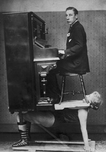 A circus strongwoman balances a piano and pianist on her chest, circa 1920. (Photo by FPG/Hulton Archive/Getty Images)