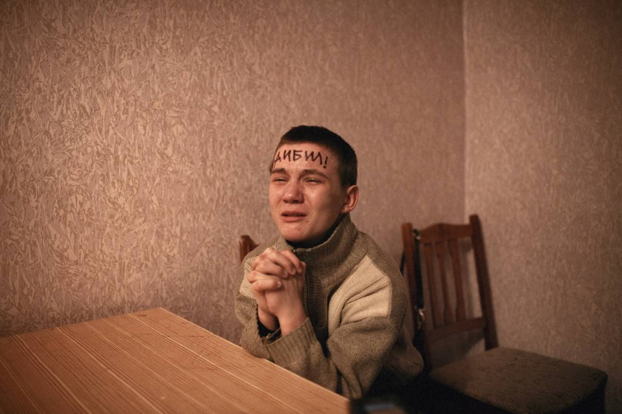 "Vitaly, 15, a chronic petty thief, truant from school and violent towards his grandmother and mother, brought in for questioning again for his role in stealing car stereos. The police wrote ""Ya Debil"" on his forehead, meaning ""I'm an imbecile"" in Russian. Vitaly has not been in school for months and his crimes have escalated. Once he turns 16, Vitaly will be sentenced as an adult and will go to prison for any future crime. The police believe that their methods will help him turnaround and stop committing crime."