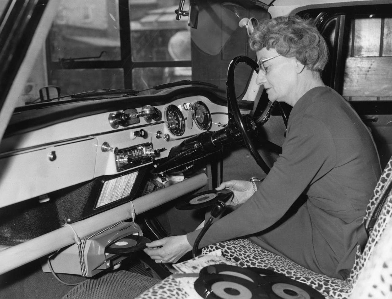 Mrs Batt inserting a record into the front of her in-car record player. The music is fed into the car radio speaker system. (Photo by Fox Photos/Getty Images)