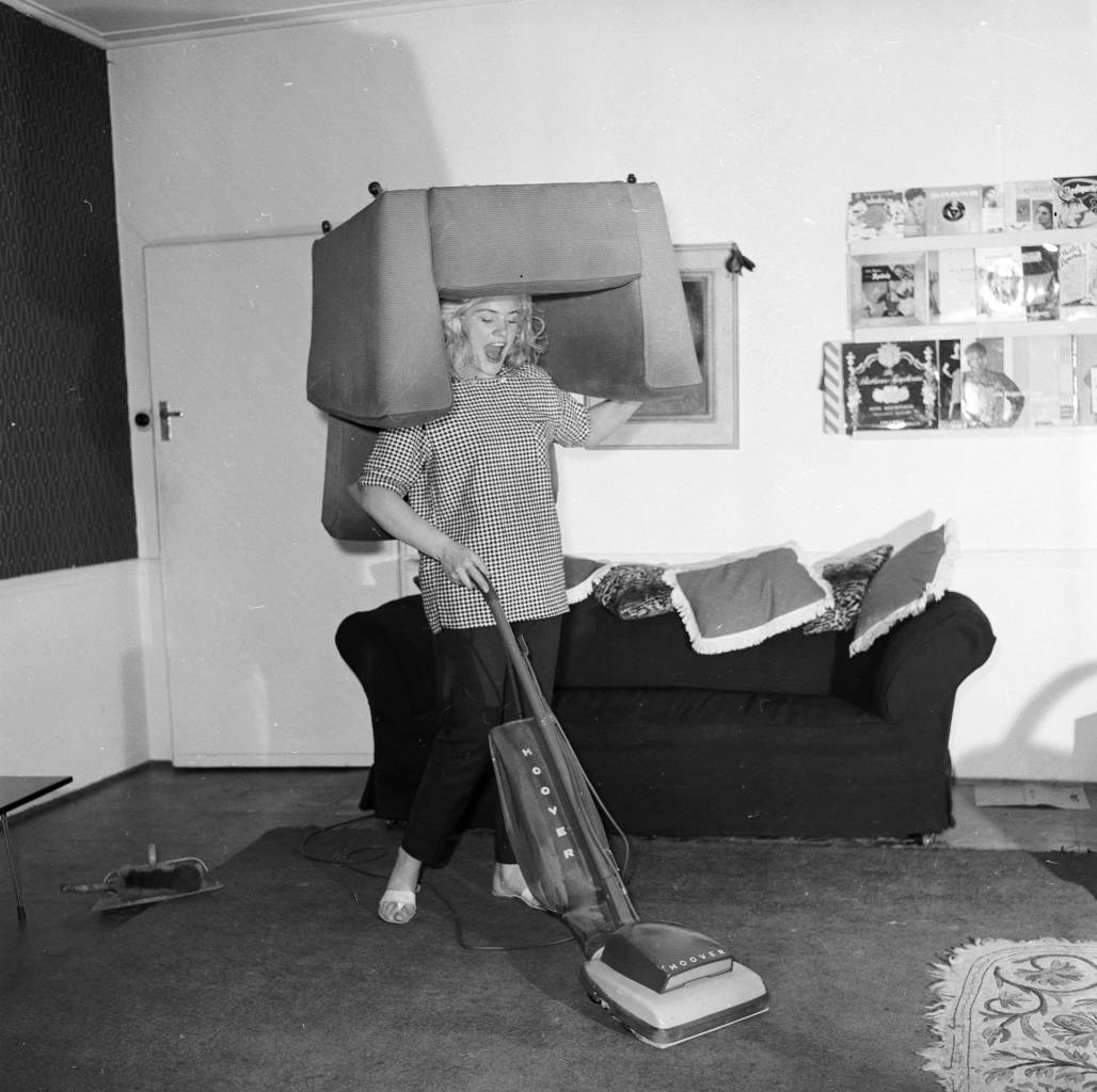 March 1958: Glamorous strongwoman Joan Rhodes exercises her strength whilst hoovering in her flat in Hampstead, north London. (Photo by Ken Harding/BIPs/Getty Images)