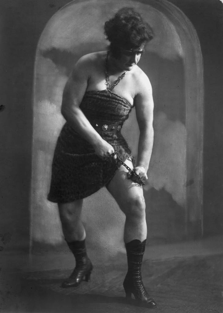 circa 1895: Strong woman, Katie Sandwina mother of boxer Teddy Sandwina, prepares to break a chain over her thigh. (Photo by General Photographic Agency/Getty Images)
