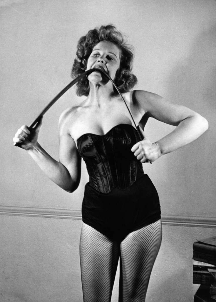 March 1950: Strongwoman Joan Rhodes bends an iron bar between her teeth. (Photo by George Konig/Keystone Features/Getty Images)