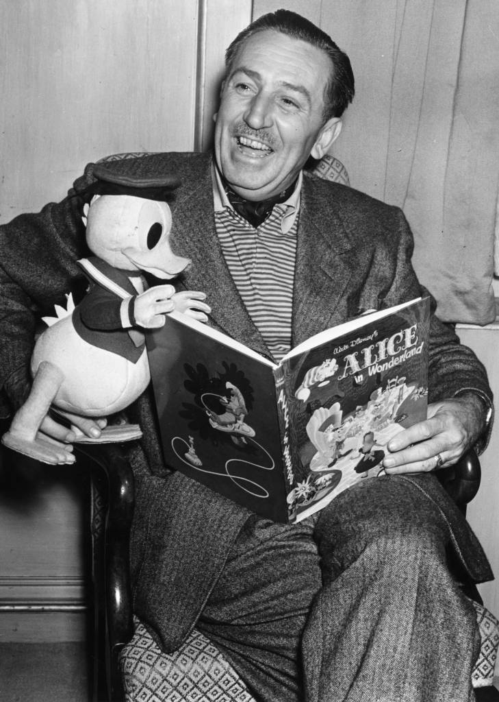 22nd June 1951:  Creator of Mickey Mouse Walt Disney (1901-1966) arrives in London to see the premiere of his latest film.  He holds a model of his character Donald Duck whilst looking at a copy of the Walt Disney book of the new film 'Alice In Wonderland'.  (Photo by Edward G. Malindine/Topical Press Agency/Getty Images)