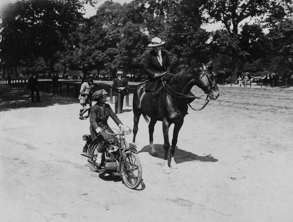 June 1921:  A woman riding a horse alongside a woman on a motorcycle in Hyde Park, London.  (Photo by Topical Press Agency/Getty Images)