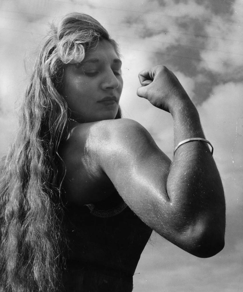September 1953: Twenty-one year old Alice Penfold, a professional strong woman from Bury, near Pulborough, Sussex, flexes her biceps. She can tear telephone directories in half and lift a 146 lb woman with her teeth. (Photo by Chris Ware/Keystone Features/Getty Images)