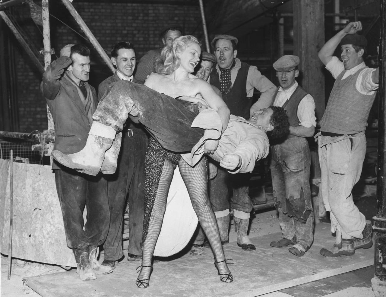8th April 1958: Men, working on the site of Quaglino's new banqueting rooms, look on in amazement as strong-woman Joan Rhodes demonstrates her strength by lifts one of their co-workers. She is appearing in cabaret at Quaglino's restaurant and decided to visit the men working next door. (Photo by Reg Speller/Fox Photos/Getty Images)
