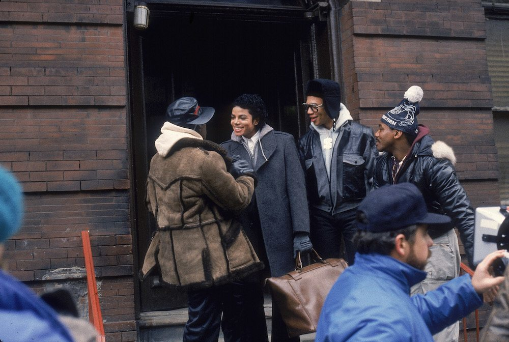 "Popular American musician Michael Jackson (1958 - 2009) (center, without hat) shakes handswith an ""Mini Max"" played by Wesley Snipes as others watch during the filming of a scene in the long-form music video for his song 'Bad,' directed by Martin Scorsese, New York, New York, November 1986. (Photo by Vinnie Zuffante/Hulton Archive/Getty Images)"