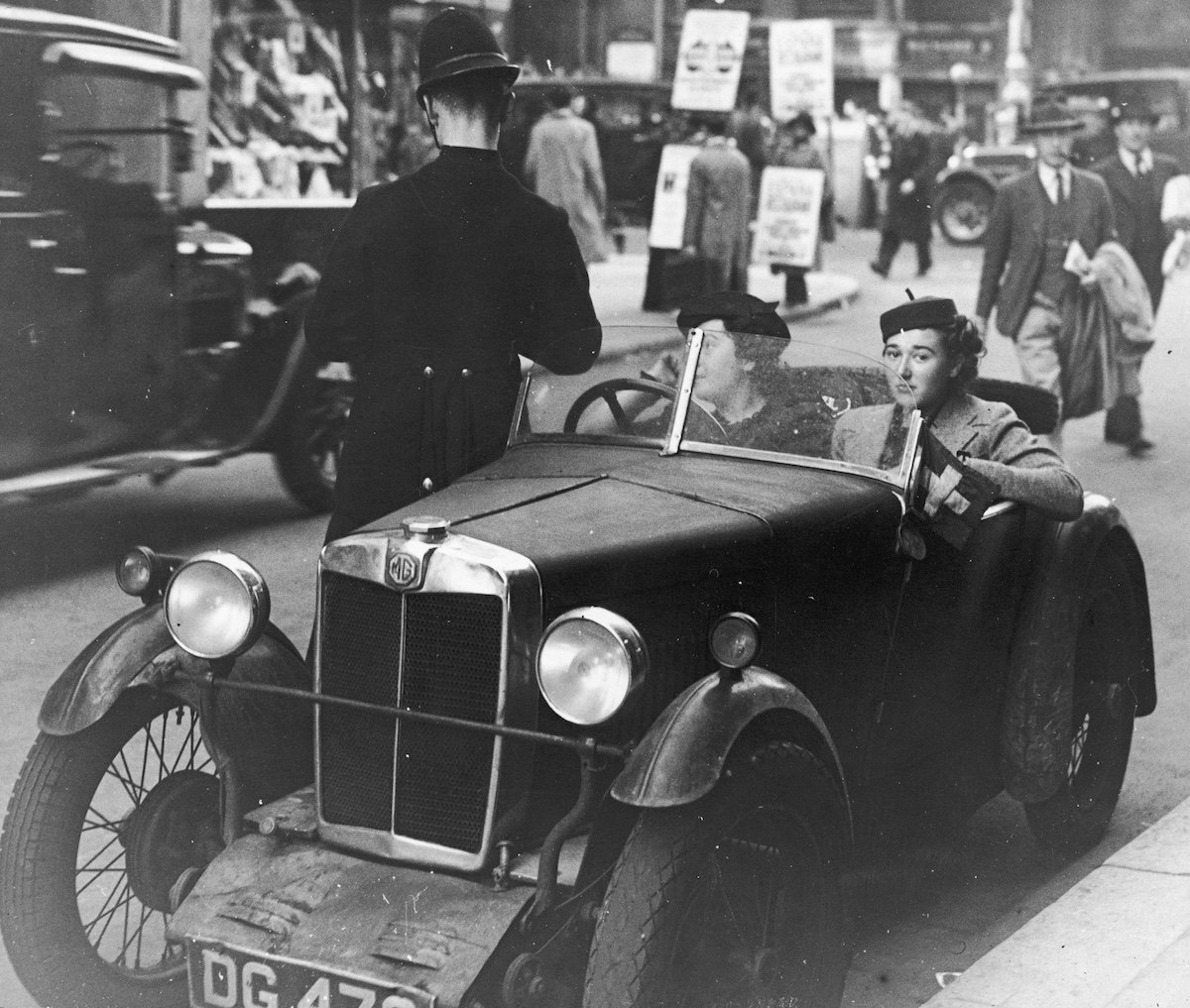 London motorists in an MG M-type receive a ticket from a traffic policeman on the corner of Wardour Street.    (Photo by General Photographic Agency/Getty Images)