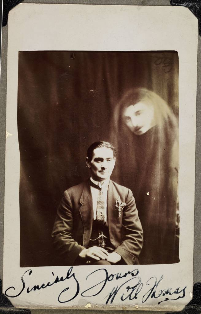 A photograph of Will Thomas, taken by William Hope (1863-1933). A man's face appears in a haze of drapery on the right of the photograph. Thomas, a medium from Wales, did not recognise the superimposed image. Thomas has signed the bottom of the photograph, 'Sincerely Yours Will Thomas' – perhaps this indicates a friendship with Hope. Hope's spirit album photographs use double and even triple exposure techniques to render the appearance of ghostly apparitions around the sitter. Hope founded the spiritualist society known as the Crewe Circle and his work was popular after World War One when many bereaved people were desperate to find evidence of loved ones living beyond the grave. Although his deception was publicly exposed in 1922, he continued to practice.