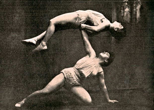 The Braselly Sisters were a pair of strongwomen who specialized in graceful and artistic strength stunts. They were also sisters of the even more famous female athlete, Sandwina. Here the two ladies do an adagio (acrobatic balancing) act. The photo found its way into The Police Gazette in 1909 where it was titled 'Muscles and Music.' The editors asked rhetorically, 'But don't you think the lady athletes are a stunning pair of statuesque beauties?'