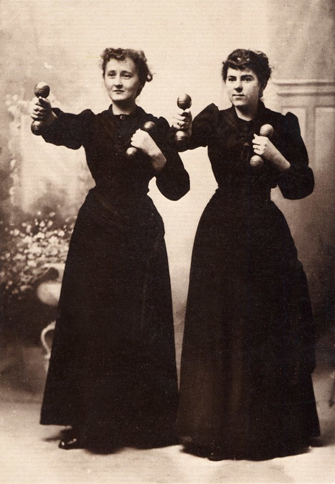 When women first began to work out with weights, it was considered dangerous to have them lift anything heavy and so they were given only two- or four-pound wooden dumbbells. The fact that women lifted much heavier objects in the home seems to have escaped most of the men who designed the exercise. here two cheerful ladies work out in their street clothes in a photograph c. 1910 by Willis T. White.