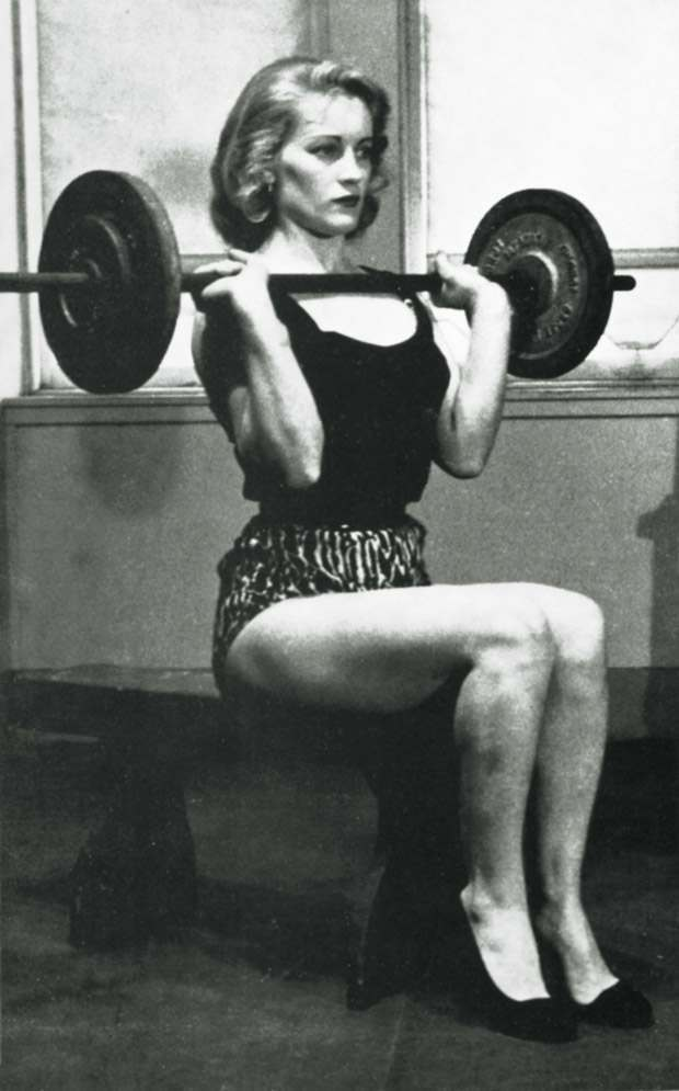 From the mid-1950s to the early 1970s, women had to appear as ladylike as possible, even when doing something as traditionally masculine as working out with weights. This girl is doing a seated press with respectably heavy weight, but her high heels and helmet-like hairdo are like fig leaves preserving her femininity.