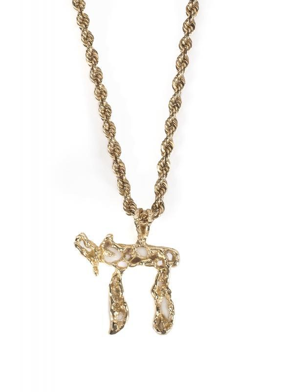 """A 14K gold Chai symbol and 14K gold rope chain, purchased and worn by Elvis Presley on stage and at Graceland. Accompanied by a signed letter of authenticity from Presley's cousin Donna Presley Early, stating that the gold Jewish symbol belonged to Elvis, and he wore it to """"cover all his bases,"""" and a letter from the Elvis-A-Rama Museum detailing the history of the pendant. Elvis can be seen wearing this or a similar Chai necklace in his last concert in 1977 below."""