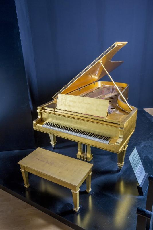 A 1928 Kimball Piano Company grand piano plated with 24K gold leaf and played by Elvis Presley while in the music room of his Graceland home in Memphis, Tennessee. The piano's original finish was walnut, and it was once housed in the Dixon-Myers Hall, now the Cook Convention Center, in Memphis. Presley purchased the piano for his mother in 1955 when the city of Memphis sold the piano, and had it moved to his new home on Audubon Drive when it would not fit into their apartment. The piano was later delivered to Graceland and kept in the music room, where an Organo system was installed so that Presley could have back-up music while playing it. The piano was placed into storage after Presley's mother's death and taken out when Priscilla Presley decided to adorn the piano in 24K gold-leaf finish as a gift for the couple's first wedding anniversary. The piano was again placed back into the music room in Graceland. Since 1977, the piano has had a few different owners, although it continued to be on public display at Graceland when it opened. The current owners have had the piano since 2009. The piano is featured in various Graceland tour documentaries, including one hosted by Priscilla Presley. Accompanied by a copy of a letter from C.B. Coltharp, who has played a part in servicing, tuning, and moving the piano; a copy of a letter from Thomas A. Hames from Hames and Sons Piano Craftsman, who tuned and installed new hammers and dampers on the piano; copies of the bills of sales; a hardcover copy of Elvis World (Knopf, 1987) by Jane and Michael Stern that shows a photograph of the piano at Graceland. Together with a matching piano bench. The piano is currently on exhibition at the Country Music Hall of Fame and Museum in Nashville, Tennessee. The winning bidder is responsible for shipping or pickup from the museum.