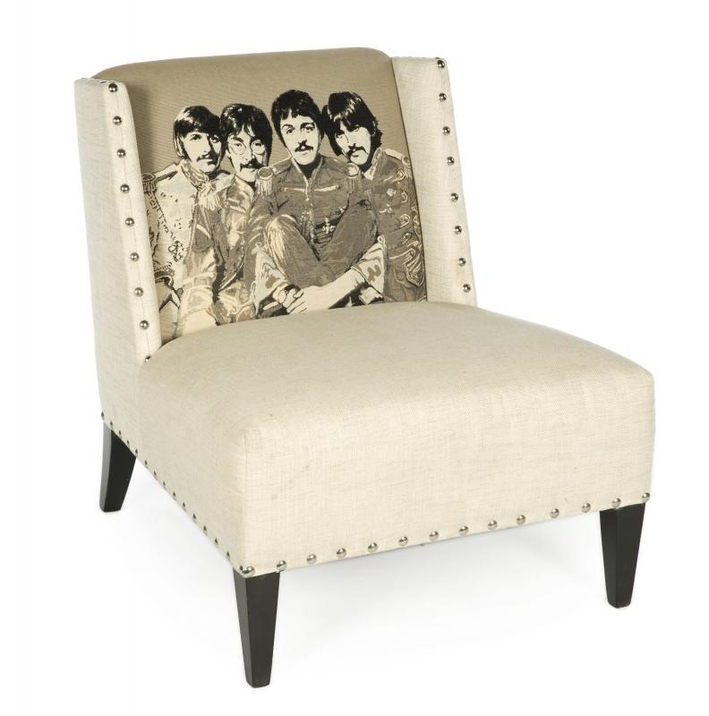 A modern upholstered chair with a tapestry depiction of the Beatles from the album cover artowrk of Sgt . Pepper's Lonely Hearts Club Band .