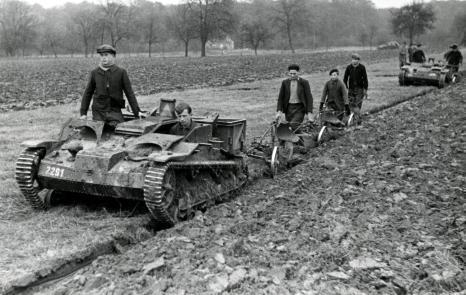 Second World War. German soldiers in tankette (little tank) are helping French farmers plough their fields. France, 1941. [Tankette: little tank (Renault), captured by German forces and used for various tasks].