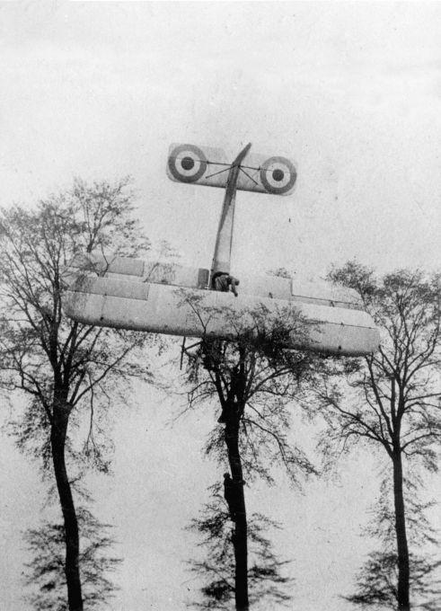 First World War , Belgium , air war . A French pilot makes an emergency landing on private property after a failed attack on German Zeppelin hangars at Brussels , 1915. The aircraft, a biplane , has ended up in the trees. Soldiers climb the tree .
