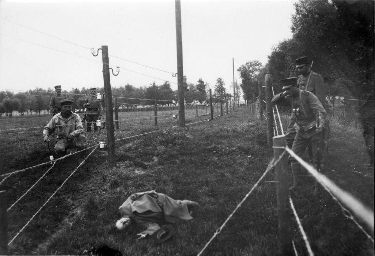 The Great War. The 'Wires of Death'. Barbed wire entanglement at the border between the Netherlands and Belgium during the First World War near Sluis in Zeeland, the Netherlands. German soldier posing as casualty. 1915.