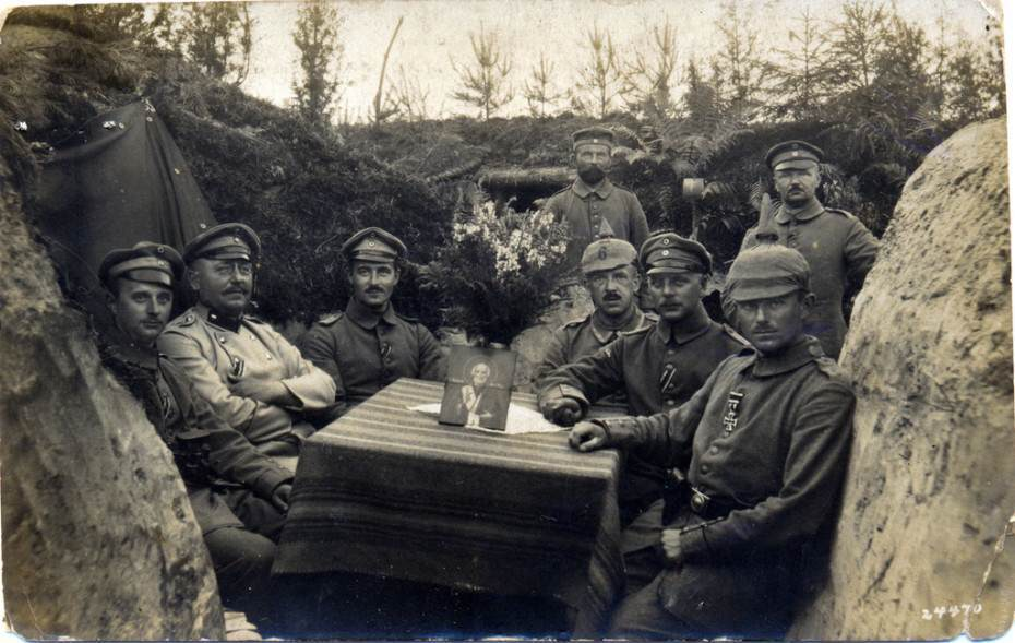 Landwehr Regiment Officers and NCOs seated around a table on which sits a portrait of a Saint Nicholas and a vase of flowers. Possibly a special occasion such as an award presentation, 1915. (c) Drake Goodman.