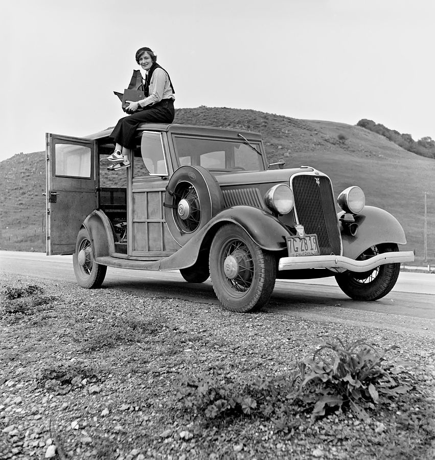 Dorothea Lange atop automobile in California. The car is a 1933 Ford Model C, 4 door Wagon. The camera is a Graflex 5x7 Series D. Lange was a New Deal Resettlement Administration and FSA-OWI photographer.