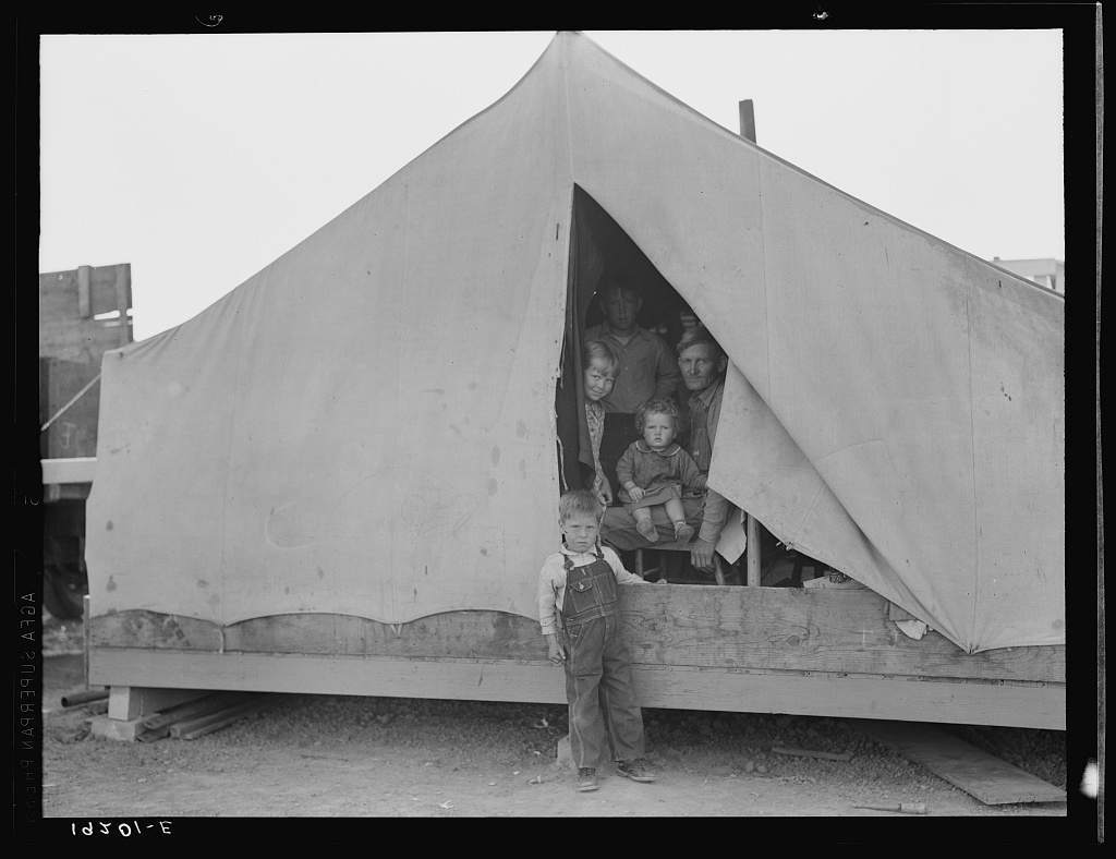"""Brawley, Imperial Valley. In Farm Security Administration (FSA) migratory labor camp. Family of mother, father and eleven children, originally from near Mangrum, Oklahoma, where he had been tenant farmer. Came to California in 1936 after the drought. Since then has been traveling from crop to crop in California, following the harvest. Six of the eleven children attend school wherever the family stops long enough. Five older children work along with the father and mother. February 23, two of the family have been lucky and """"got a place"""" (a day's work) in the peas on the Sinclair ranch. Father had earned about one dollar and seventy-three cents for ten-hour day. Oldest daughter had earned one dollar and twenty-five cents. Form these earnings had to provide their transportation to the fields twenty miles away. Mother wants to return to Oklahoma, father unwilling.She says, """"I want to go back to where we can live happym live decent, and grow what we eat."""" He says, """"We can't go the way I am now. We've got nothing in the world to farm with. I made my mistake when I came out here."""""""