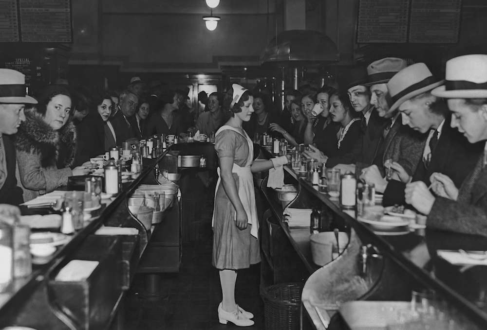 A waitress stands in the middle of the counters during lunch time at the Exchange Buffet in New York City in the 1920's. (Photo by Keystone View/FPG/Getty Images)