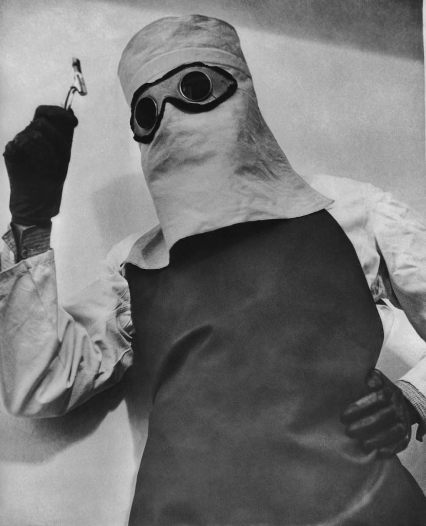 A doctor wearing a mask, shirt and apron impregnated with lead to shield him from the effects of a vial of radium in 1936. (Photo by Keystone View/FPG/Getty Images)