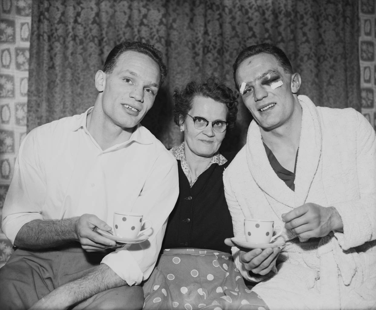 British boxer Henry Cooper (1934 - 2011, right) with his twin brother George (1934 - 2010), and their mother Lily at their home in Bellingham, south London, 13th January 1959. Henry is injured after his previous night's fight against Brian London, in which he won the Commonwealth (British Empire) heavyweight title. George boxed using the name Jim Cooper. (Photo by Reg Speller/Fox Photos/Hulton Archive/Getty Images)